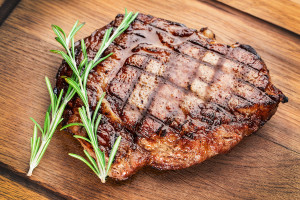 Beef steak with rosemary on a wooden table.