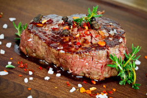 grilled steak with thyme on wooden board